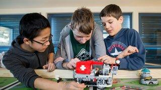 Trois écoliers pros du robot Lego