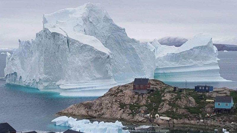 L'iceberg dépasse les toits de maisons construites sur un promontoire du village d'Innaarsuit.
