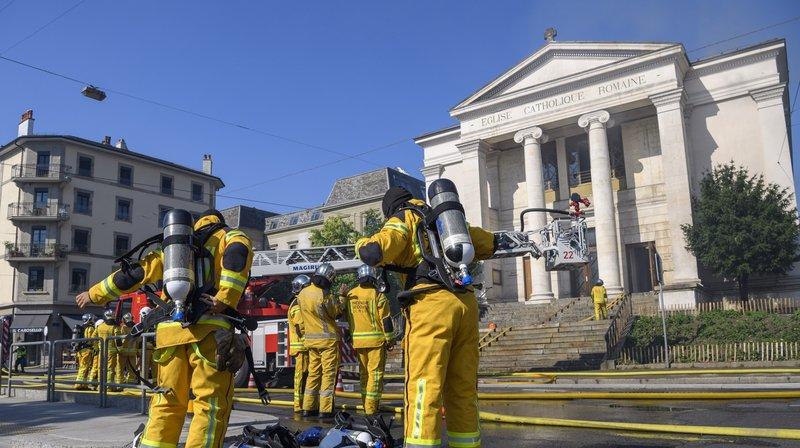 """Des pompiers du SIS (Service d'Incendie et de Secours) s'affairent sur l'incendie de l'église du Sacre Coeur située dans le quartier de Plainpalais à Geneve, le jeudi 19 juillet 2018. L'incendie a cause l'effondrement de trois niveaux de l'église du Sacre Coeur, selon les pompiers du Service d'incendie et de secours (SIS), l'effondrement de tout l'intérieur de l'édifice est """"inéluctable""""."""