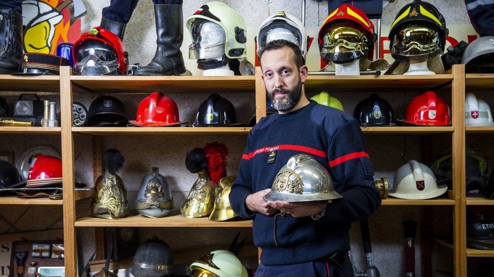 David Pagot entouré d'un échantillon de ses 200 casques de sapeurs-pompiers, provenant essentiellement de Suisse ou de France. Dans ses mains, le premier casque qu'il a porté en devenant pompier volontaire dans la commune française où il a grandi.